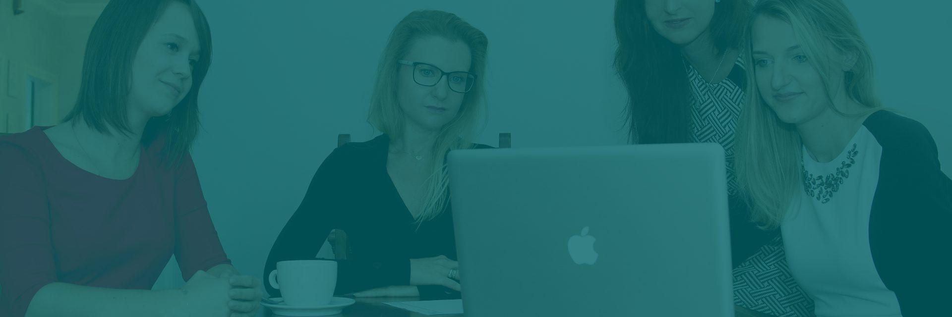 Cztery kobiety przy stole, na którym stoi komputer